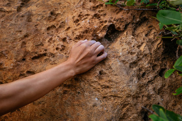 rock climber hands climbing on steep cliff