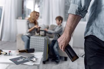 Moving. Alcohol addicted man standing with a glass bottle in his hand and looking at his beautiful serious wife packing suitcases with their son and getting ready to leave him