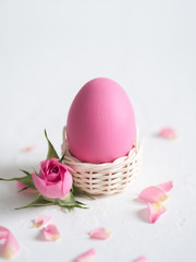 Decorative Easter eggs and pink roses on light background. Holiday card.