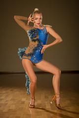 Beautiful young woman dancer in blue dress pose in ballroom