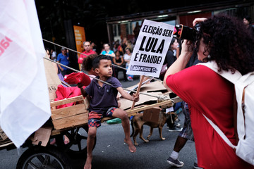 "The son of a garbage recycler holds a sign reading ""Election without Lula is fraud"" as they take part in a protest against Brazil's President Michel Temer's proposal to reform the social security system in Sao Paulo"