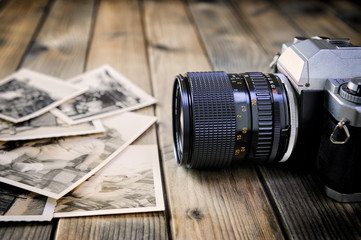 Camera film and vintage prints of aged wooden background.