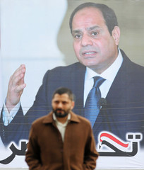 A man walks by a poster of Egypt's President Abdel Fattah al-Sisi for the upcoming presidential election, in Cairo