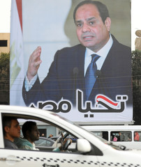 A man drives his car by a poster of Egypt's President Abdel Fattah al-Sisi for the upcoming presidential election, in Cairo