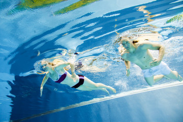 Underwater View Of A Young Couple Swimming In The Pool