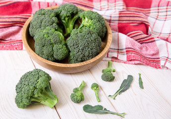 fresh green  broccoli in the wooden plate.red checkered tablecloth