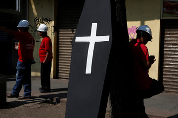 A member of the miners' union checks his phone next to a mock coffin during a protest to mark the 12th anniversary of the explosion at Grupo Mexico's Pasta de Conchos coal mine that left 65 miners dead, outside the Interior Minister building in Mexico City