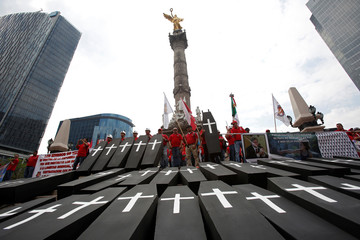 Mock coffins, symbolising the 65 miners that died in an explosion at Grupo Mexico's Pasta de Conchos coal mine, are displayed at the Angel of the Independence monument during a protest to mark the 12th anniversary of the disaster, in Mexico City