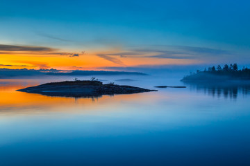 Fog over Lake. Sunrise in the fog. Wild nature of Finland. Islands of stone. Mirror reflection in water. Summer in Finland.