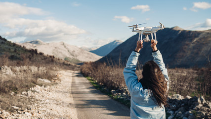 Young woman videographer catching flying aircraft with camera.Controlling landing of drone.Female filmmaker in nature using quad copter aircraft to capture landscape.Assisting drone landing.