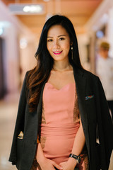 Portrait of a young Chinese Asian fashionista, blogger or influencer woman standing indoors and smiling. She is wearing an elegant pink dress and has a man's jacket draped over her shoulders.