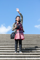 A young woman tourist with a camera standing on the stairs and waving hands. Girl traveler on the stairs with a horizon of blue sky.