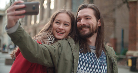 Couple taking phone picture together in a city street.
