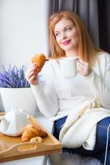 A woman drinks tea and has croissants with jam. Frozen bun.