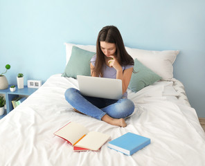 Cute teenager girl using laptop while doing homework in bedroom