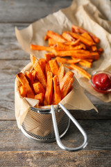 Deep fry basket with sweet potato fries on wooden table