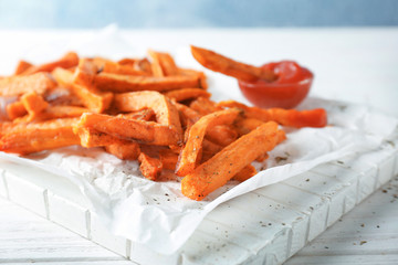 White board with tasty sweet potato fries on wooden table, closeup