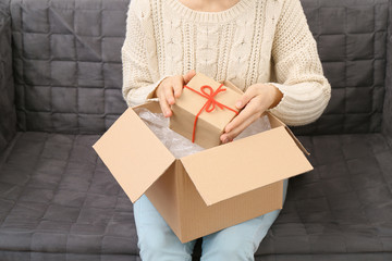 Woman taking gift box out of parcel at home