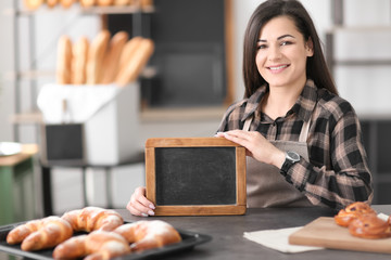 Portrait of young woman with mini chalkboard in bakery. Small business owner