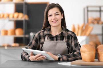 Young woman using tablet computer in bakery. Small business owner