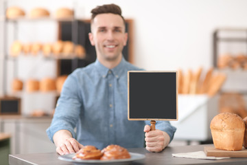 Portrait of young man with mini chalkboard in bakery. Small business owner