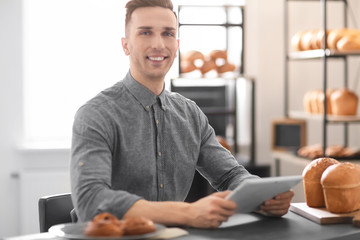 Young man using tablet computer in bakery. Small business owner