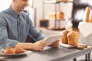 Man using tablet computer in bakery. Small business owner