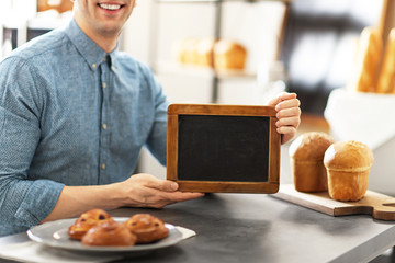Man holding mini chalkboard in bakery. Small business owner