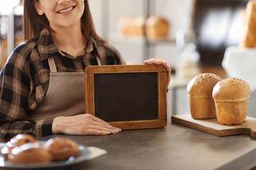 Woman holding mini chalkboard in bakery. Small business owner