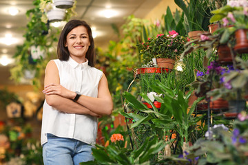 Portrait of young woman in greenhouse. Small business owner