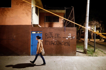 """A man walks past a graffiti reading """"Evacuation route"""" at a makeshift shelter for families affected by the earthquake that hit the Tlalpan housing project, five months after the September 19 earthquake, in the Educacion neighborhood in Mexico City"""