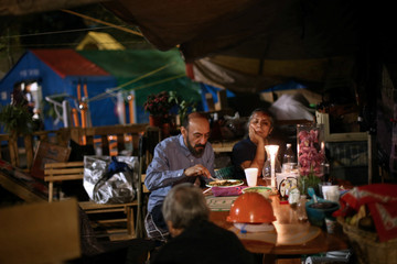 People eat in a makeshift shelter for families affected by an earthquake in the Tlalpan housing project, five months after the September 19 earthquake, in the Educacion neighborhood in Mexico City