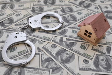 iron handcuffs, a house made of wood on a background of American dollar bills. illegal sale of property. swindle. economic crimes.