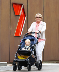 A woman walks with a baby in front of the Channel 7 logo in Sydney