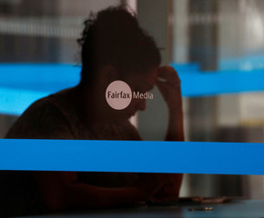 A woman sits at a table inside the Fairfax Media building in Sydney