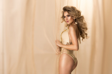 Sensual blonde woman posing in gold sexy lingerie , looking at camera.