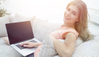 beautiful young woman working with laptop sitting on sofa and lo