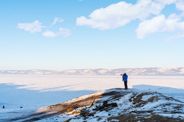 Traveller photographer taking photograph on cliff at lake Baikal, Russia in winter