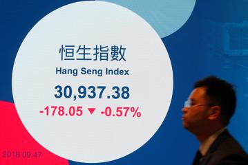 A man walks past a panel displaying the morning trading index at Hong Kong Exchanges in Hong Kong