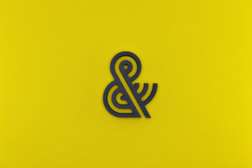 black ampersand with parallel lines on yellow background