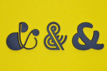 three black ampersand characters on yellow background