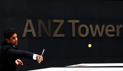 An office worker plays table tennis in front of an ANZ Banking corporation tower in central Sydney