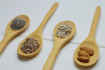 four wooden spoons with seeds