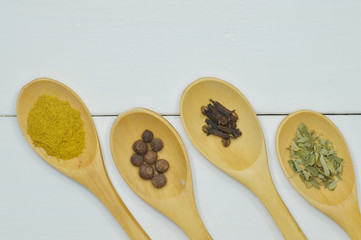four wooden spoons with spices top view