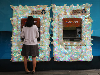 A woman uses an ANZ Banking corporation ATM in central Sydney