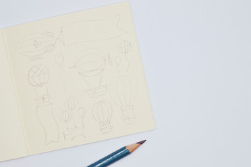 notebook with pencil sketches of balloons on white background