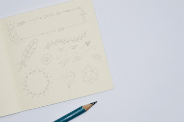 notebook with pencil sketches of feathers and arrows on white background
