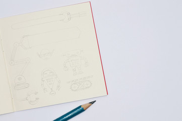 notebook with pencil sketches of robots on white background