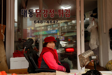 A street vendor sits at her stall at Jungang market in Gangneung