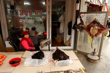A street vendor sells dried fish at the Jungang Market in Gangneung